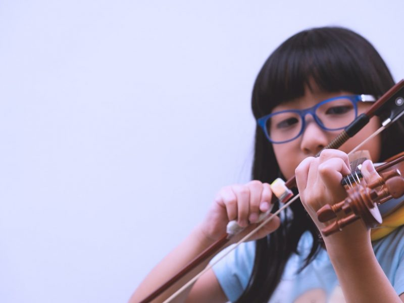 A Thai little girl with long black hair and eyeglasses practicing violin in beginning level class