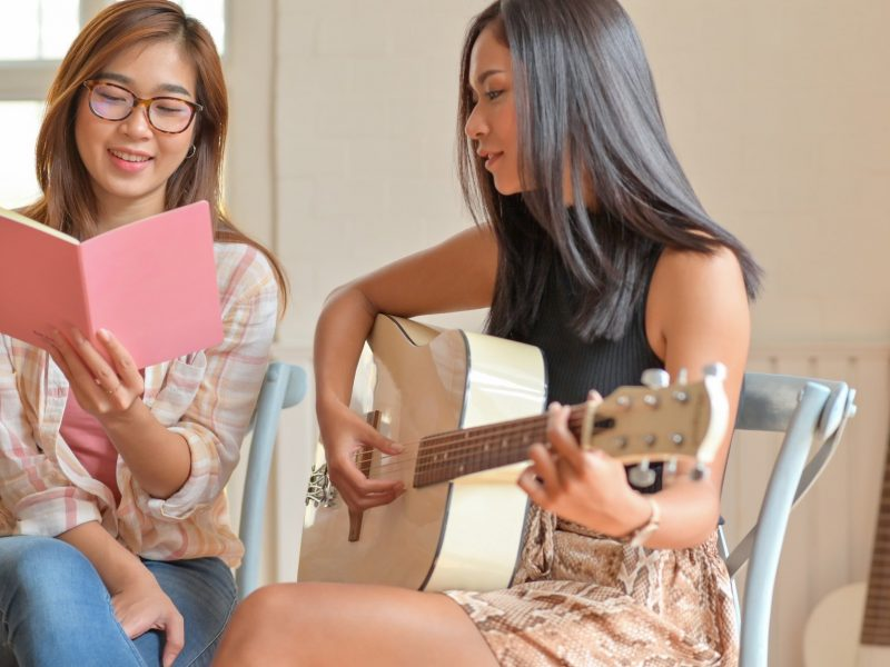 Two young women playing guitar and singing happily.