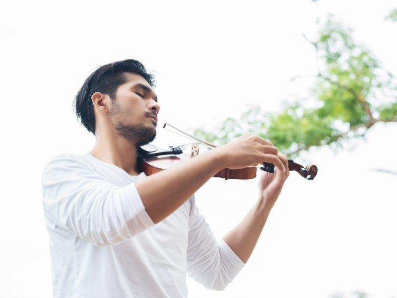 Young hipster musician man play violin in the nature outdoor lifestyle behind mountain.